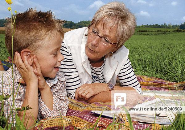 Oma liegt mit Enkelsohn auf Wiese