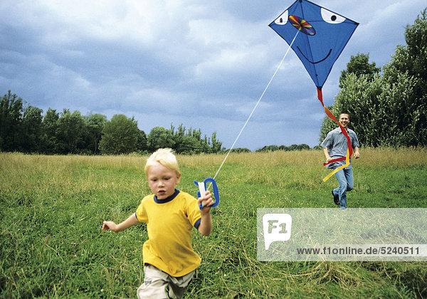 Kleiner Junge lässt mit Vater Drachen steigen
