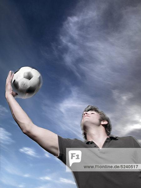 Junger Mann wirft Fußball in die Luft