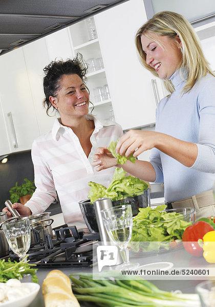 Zwei Frauen in der Küche  bereiten Salat zu