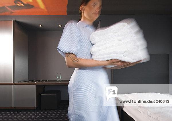 Zimmermädcehn mit einem Stapel Handtücher  Bewegung