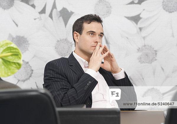 Mann sitzt am Schreibtisch  nachdenklich
