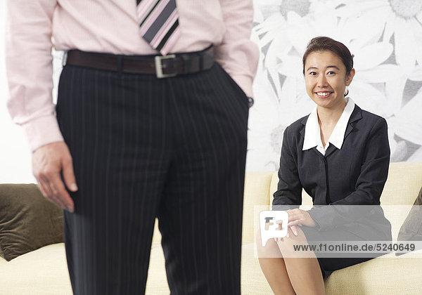 Frau  Asiatin  sitzt lächelnd auf Sofa  Mann steht abgewand davor