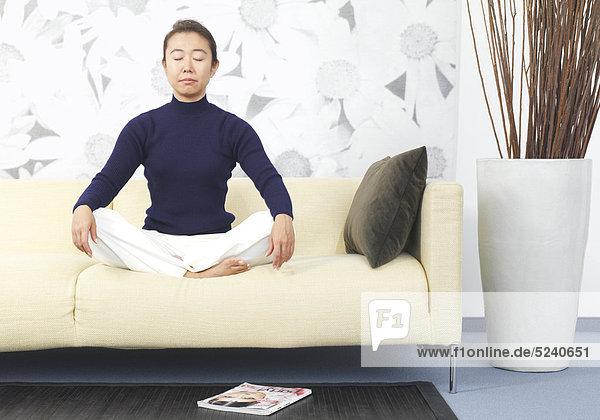 Frau  Asiatin  sitzt im Schneidersitz auf Sofa  meditiert