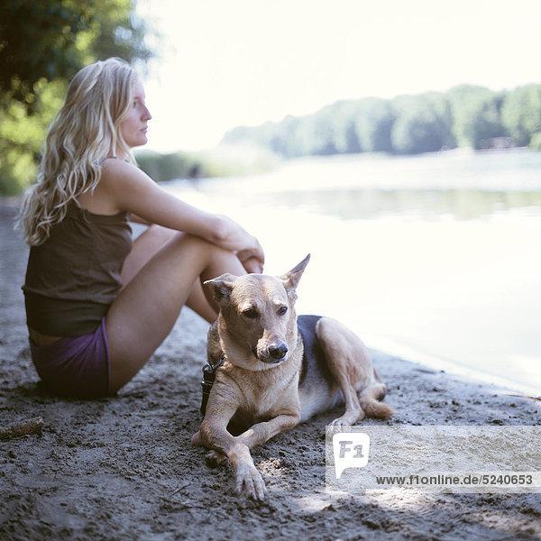 Frau sitzt mit Hund an Seeufer