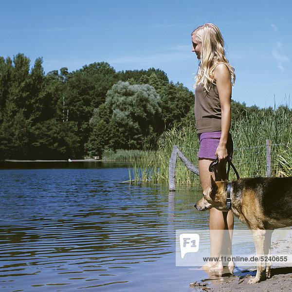 Frau steht mit Hund an Seeufer