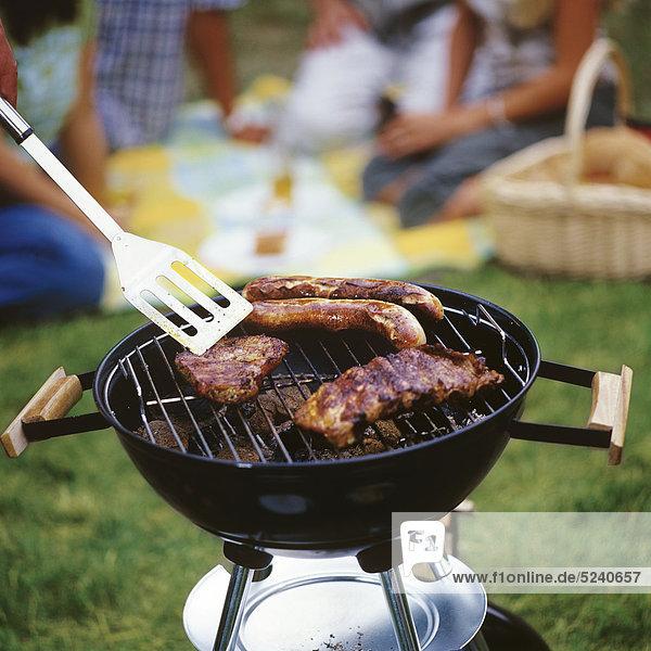 Steaks und Bratwürste auf Grill  Leute im Hintergrund