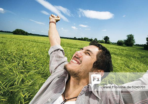 Mann steht mit ausgestreckten Armen in Getreidefeld  freut sich
