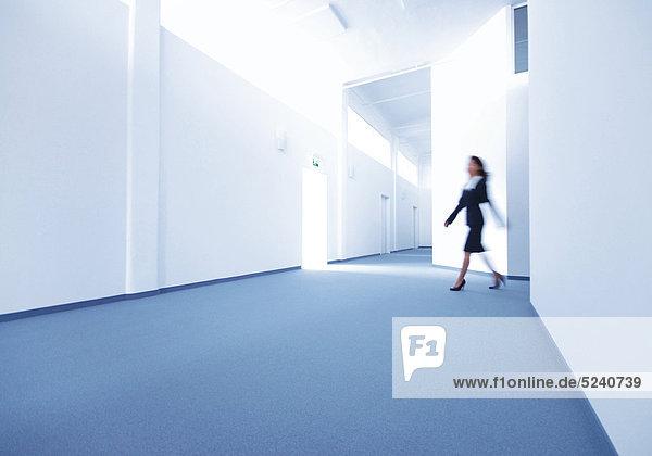 Frau geht über Gang eines Bürogebäudes
