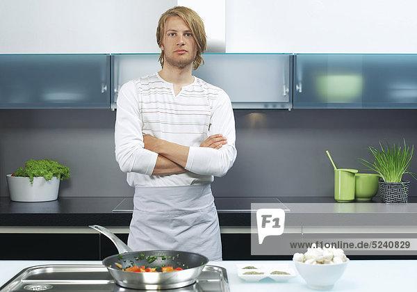 Junger Mann steht mit verschränkten Armen in Küche