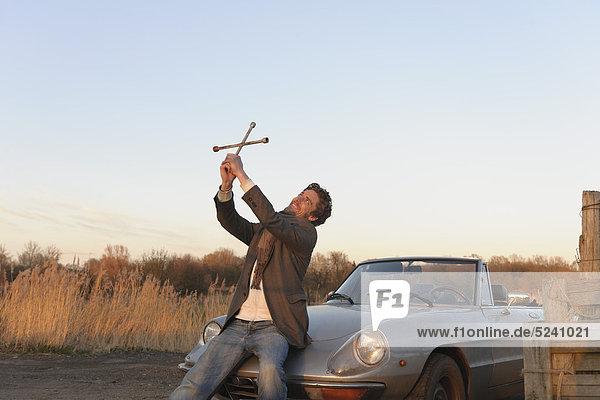 Mann mit Laschenschlüssel als Kreuz in der Nähe eines klassischen Cabriolets