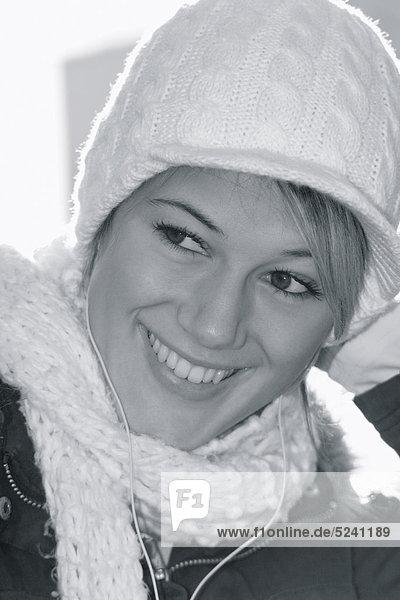Junge Frau mit Mütze  Schal und MP3-Player  Porträt