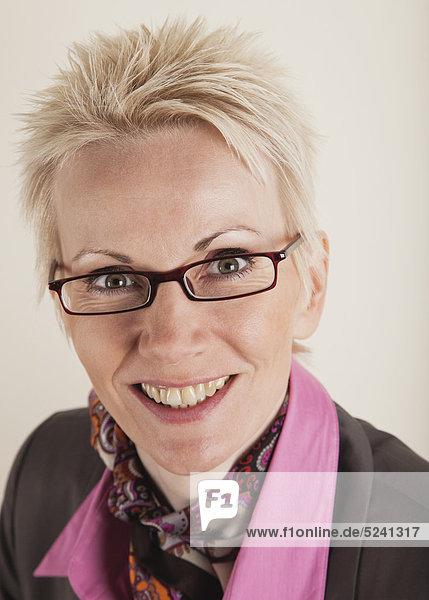Nahaufnahme einer reifen Frau im Business-Anzug vor weißem Hintergrund  lächelnd  Portrait