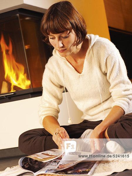 Junge Frau liest vor Kaminofen am Boden Zeitschrift