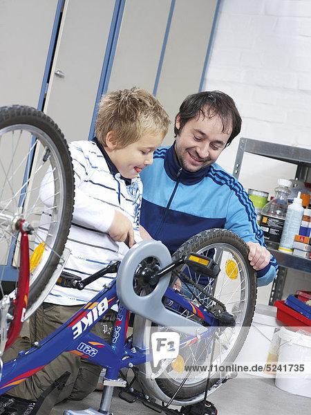 Vater und Sohn reparieren Fahrrad  Junge schraubt Rad fest