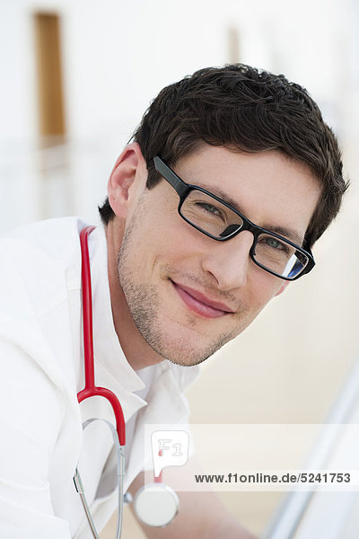 Germany  Bavaria  Diessen am Ammersee  Close up of young doctor leaning on railng with sethoscope  smiling  portrait