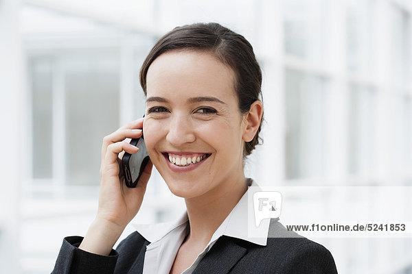 Diessen am Ammersee  Junge Geschäftsfrau am Handy  lächelnd  Portrait