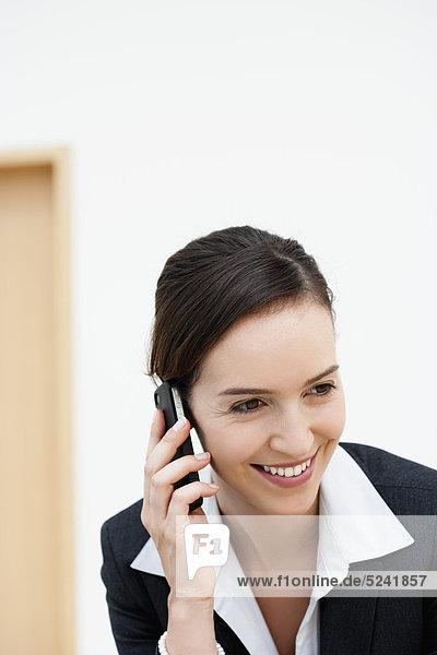 Diessen am Ammersee  Junge Geschäftsfrau im Gespräch mit dem Handy  lächelnd