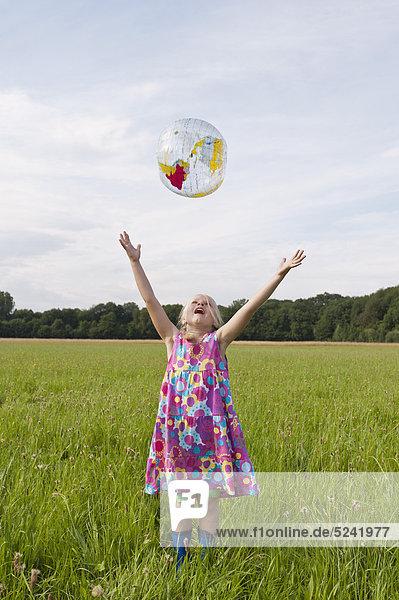 Germany  North Rhine-Westphalia  Hennef  Girl throwing beach ball globe in meadow
