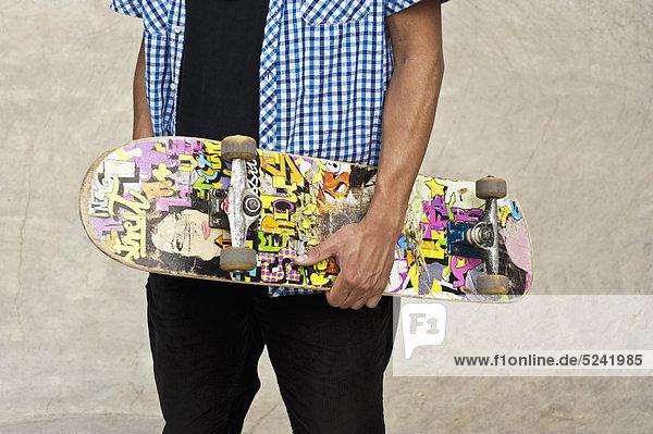 Deutschland  D_ºsseldorf  Nahaufnahme eines Skateboardfahrers mit seinem Deck im öffentlichen Skatepark