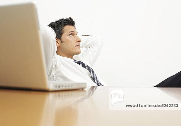 Junger Mann lehnt sich gemütlich am Schreibtisch zurück Junger Mann lehnt sich gemütlich am Schreibtisch zurück