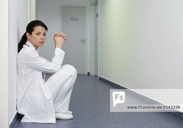 Ärztin hockt an einer Wand im Flur Ärztin hockt an einer Wand im Flur