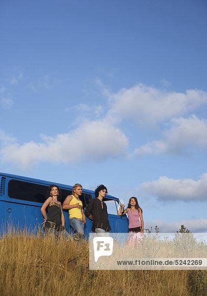 Gruppe junger Leute steht neben einem Bus Gruppe junger Leute steht neben einem Bus