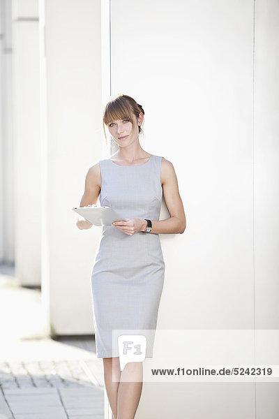 Junge Geschäftsfrau mit digitalem Tablett an die Wand gelehnt
