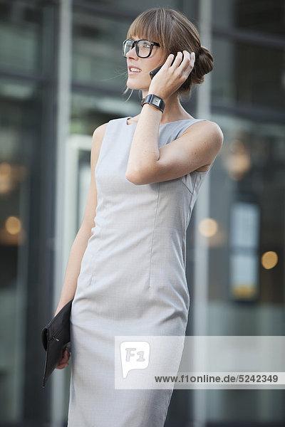 Junge Geschäftsfrau mit Brille per Handy