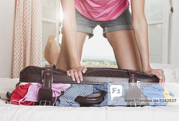 Italien  Toskana  Junge Frau schiebt Stoffkoffer in Hotelzimmer