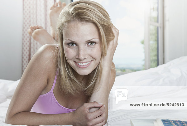 Italy  Tuscany  Young woman lying on bed in hotel room  portrait  smiling
