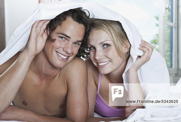 Italien  Toskana  Junges Paar liegend mit Bettlaken im Hotelzimmer