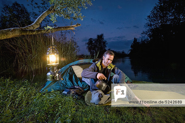 Man pouring drink near lakeshore while camping at night