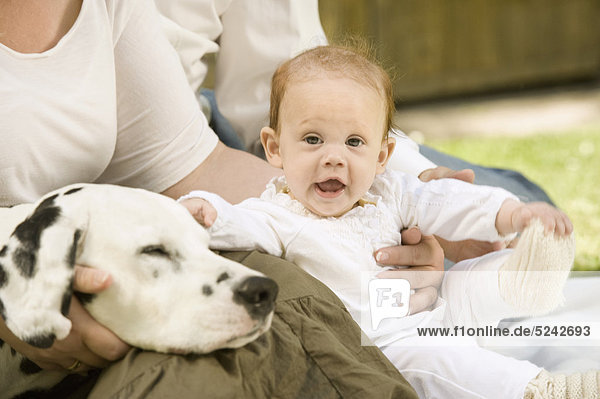 Germany  Bavaria  Father  mother and daughter with dalmatian in garden  smiling