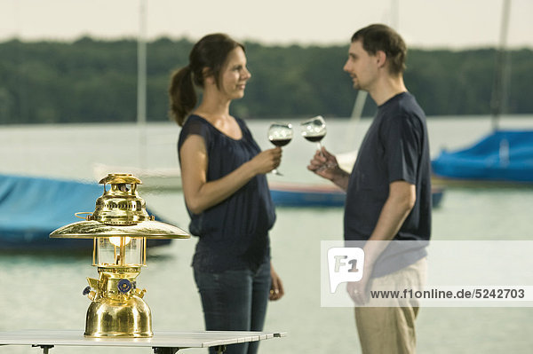 Germany  Bavaria  Woerthsee  Couple enjoying wine near lakeshore while camping with lantern in foreground
