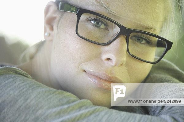 Junge Frau mit dicker Brille  lächelnd  Portrait  Nahaufnahme