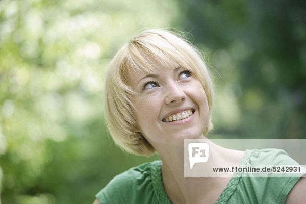 Nahaufnahme einer jungen Frau im Park  lächelnd