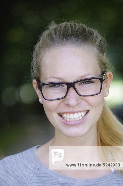 Nahaufnahme einer jungen Frau mit dicker Brille  Portrait  lächelnd
