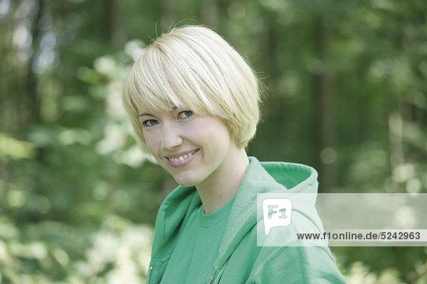 Nahaufnahme einer jungen Frau im Wald  Portrait  Lächeln