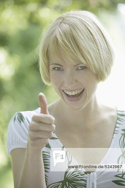 Nahaufnahme einer jungen Frau  die ihre Daumen nach oben zeigt  Porträt  Lächeln