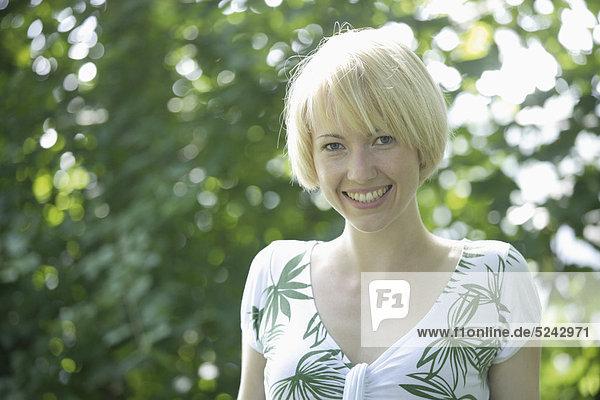 Nahaufnahme einer jungen Frau im Park  Portrait  Lächeln