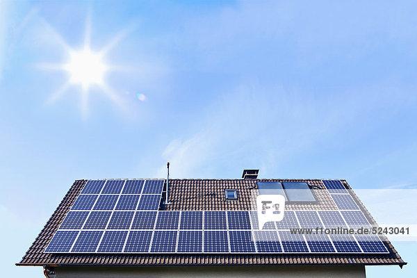 Deutschland  Solarmodule auf Hausdach vor blauem Himmel mit Sonne