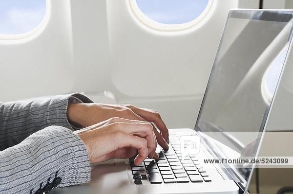 Nahaufnahme der Hand der Geschäftsfrau mit Laptop in der Business Class Flugzeugkabine