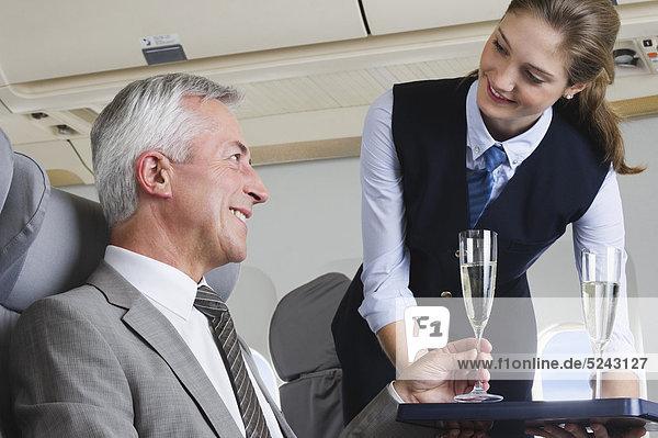 Deutschland  Bayern  München  Junge Stewardess serviert Champagner für Senior Geschäftsmann in Business Class Flugzeugkabine