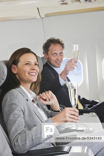 Geschäftsmann und Frau toasten Champagner in der Business Class Flugzeugkabine  lächelnd