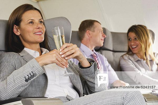 Deutschland  Bayern  München  Geschäftsleute sprechen und halten Champagner in der Business Class Flugzeugkabine  lächelnd