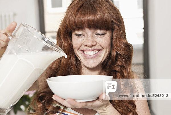 Nahaufnahme einer jungen Frau  die Getreide zubereitet  lächelnd