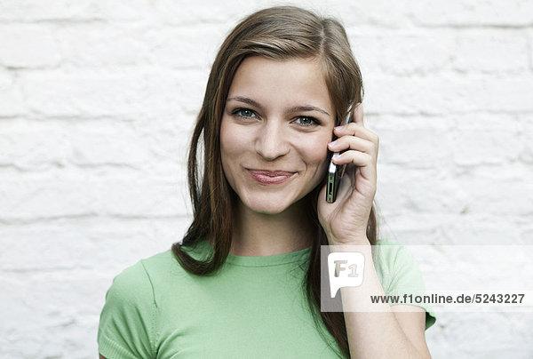 Nahaufnahme einer jungen Frau mit Handy  Portrait  Lächeln