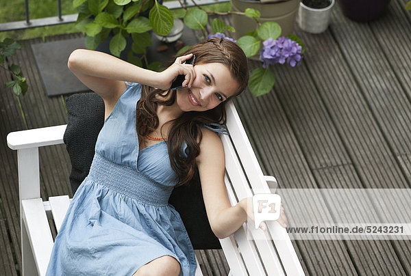 Junge Frau mit Handy auf Bank  lächelnd  Portrait