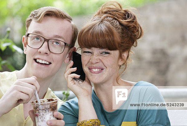 Germany  Berlin  Close up of young couple listening to cell phone  smiling